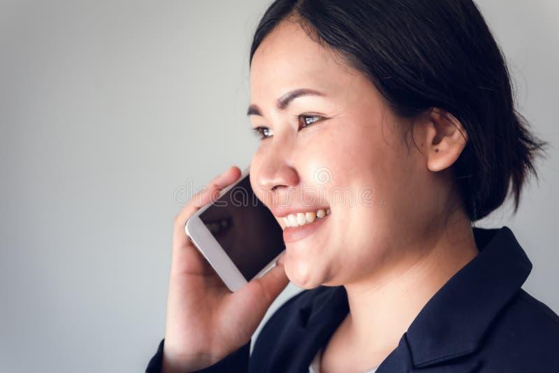 女实业家特写镜头画象拜访手机,有吸引力亚裔妇女在她智能手机和微笑谈话 免版税图库摄影