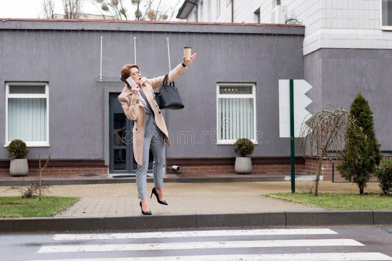 女实业家用去的咖啡谈在智能手机和呼吁出租汽车 免版税图库摄影