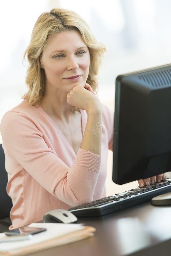 女实业家用在看计算机的奇恩角的手在办公室 免版税库存图片