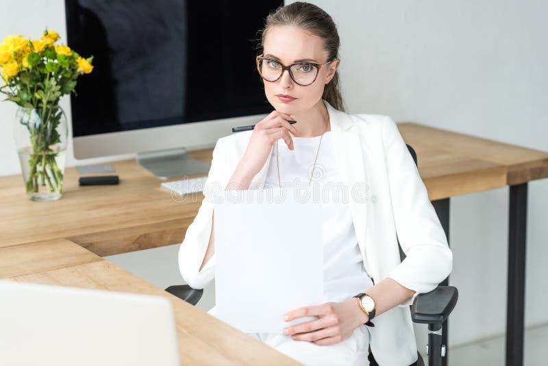 女实业家画象镜片的有在工作场所的文件的有膝上型计算机的 库存图片