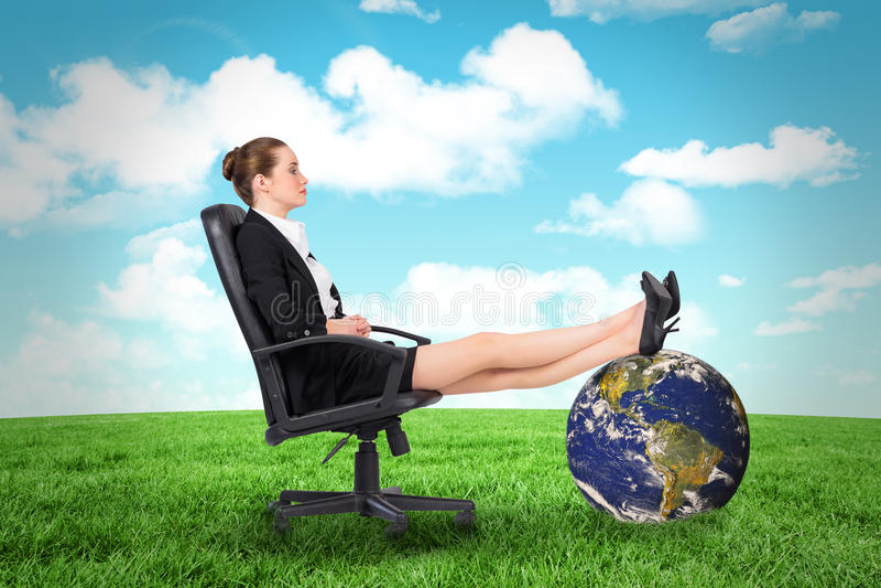 女实业家的综合图象坐与脚的转椅 免版税库存图片
