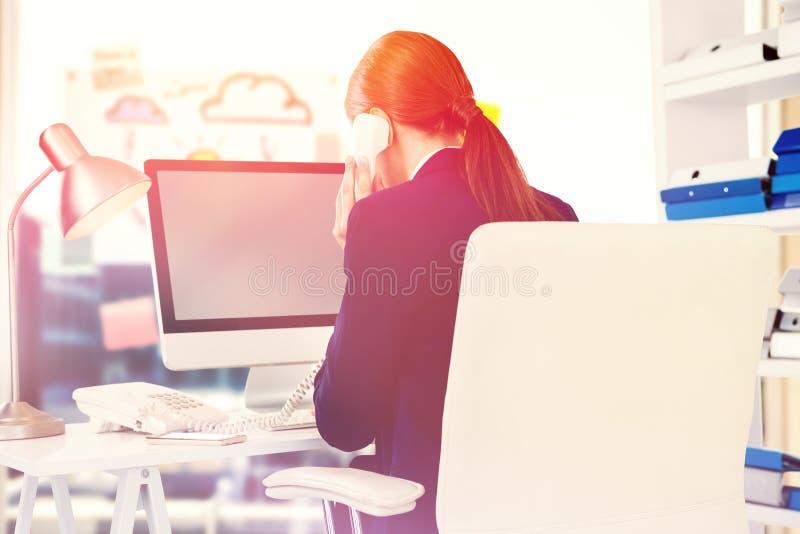 女实业家的综合图象谈话在电话在书桌在办公室 免版税图库摄影