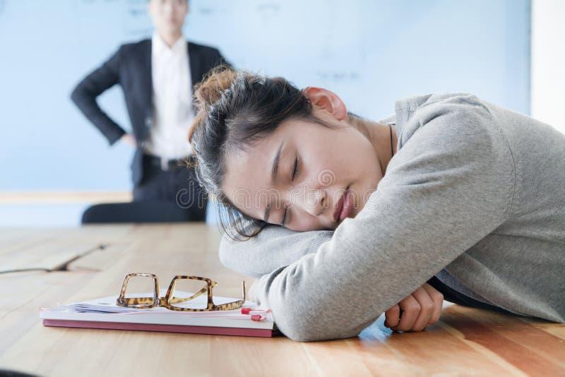 年轻女实业家睡觉在会议期间的,看她的失望的上司 免版税图库摄影