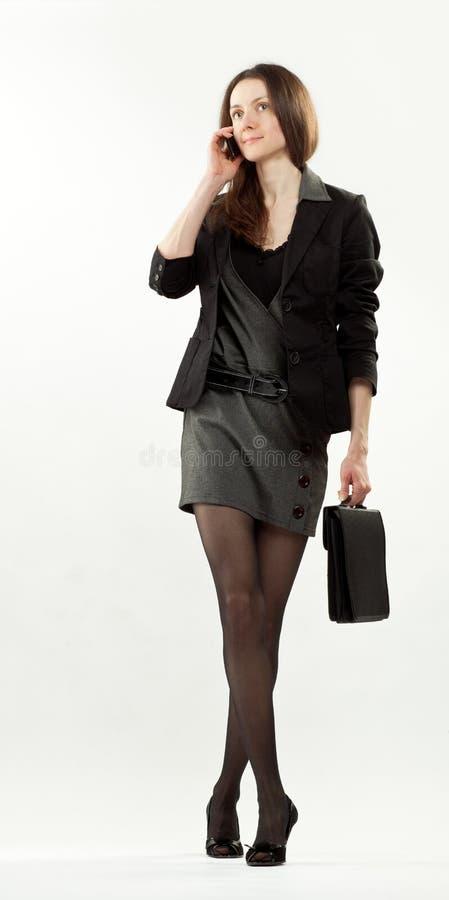 女实业家移动电话走的年轻人 免版税库存图片