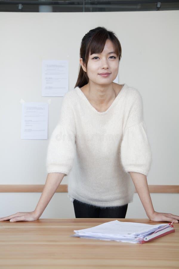 年轻女实业家站立用她的在桌上的手的,画象 免版税库存照片