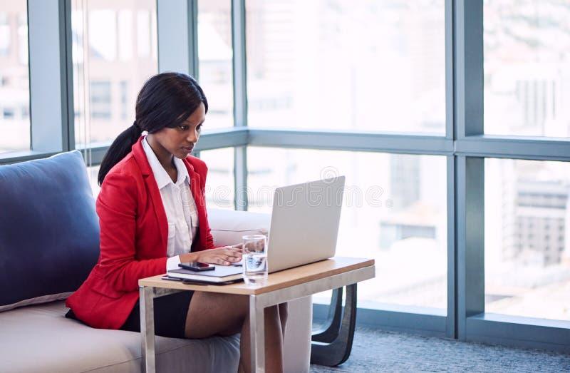 女实业家繁忙键入在她的计算机上在现代企业休息室 免版税库存图片