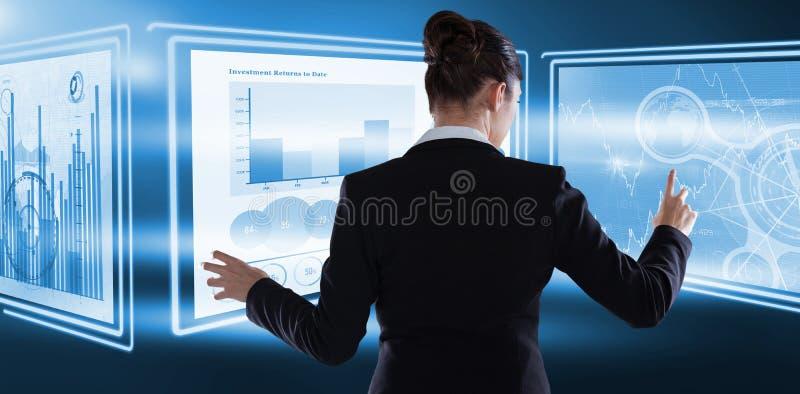 女实业家背面图的综合图象使用有想象力的数字式屏幕的  免版税库存照片
