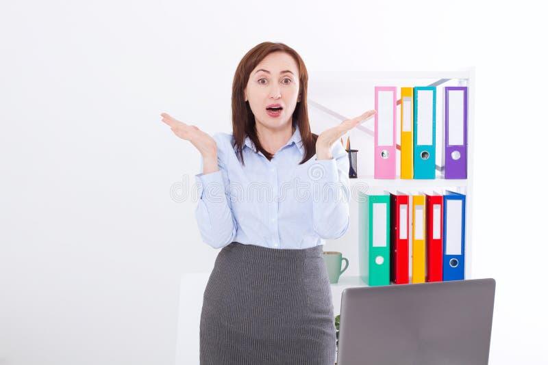 女实业家获取消极或正面新闻办公室背景 疯狂和惊奇的妇女面孔震惊,翻倒 到达天空的企业概念金黄回归键所有权 库存图片