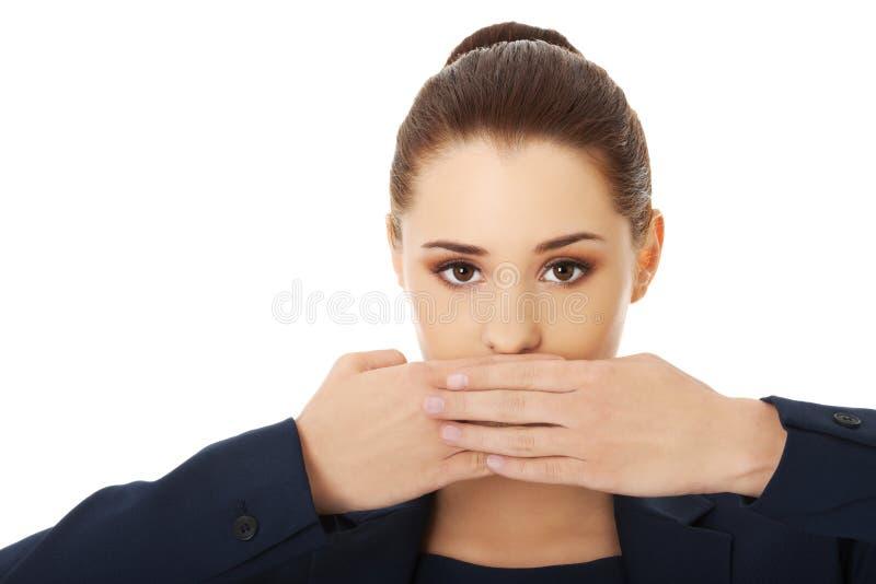 年轻女实业家覆盖物用手她的嘴 库存照片