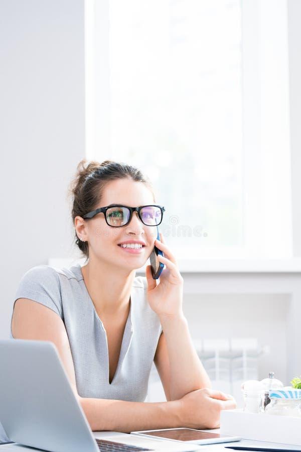 女实业家讲话由在咖啡馆的电话 库存图片