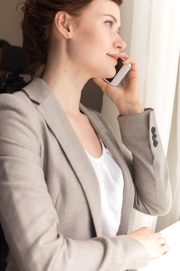 女实业家讲话由看窗口的电话 免版税图库摄影