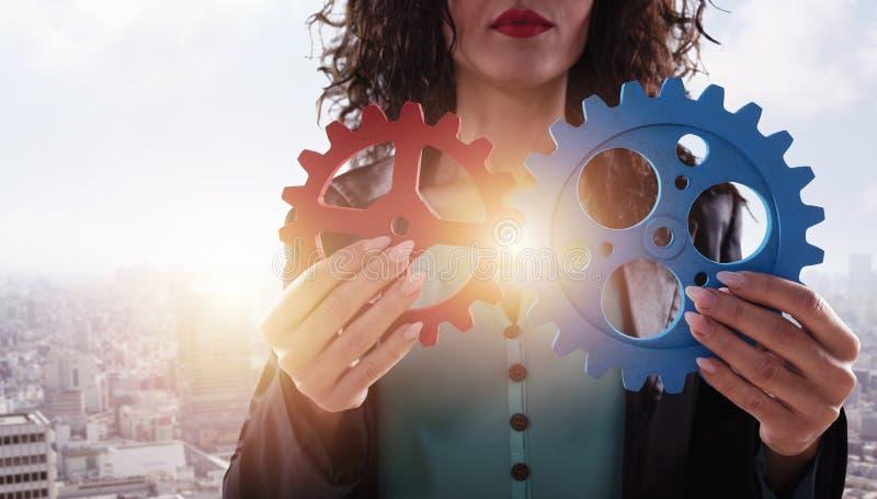 女实业家设法连接齿轮片断 配合、合作和综合化的概念 库存图片