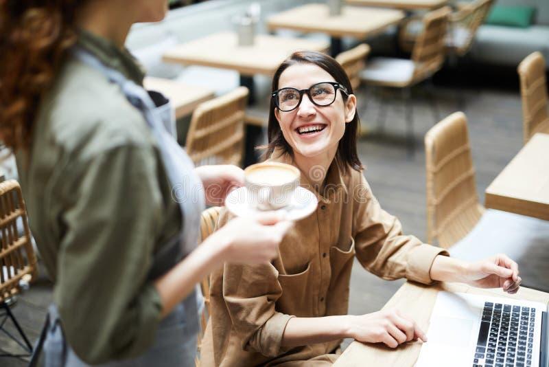 女实业家谈话与咖啡馆的女服务员 免版税库存图片