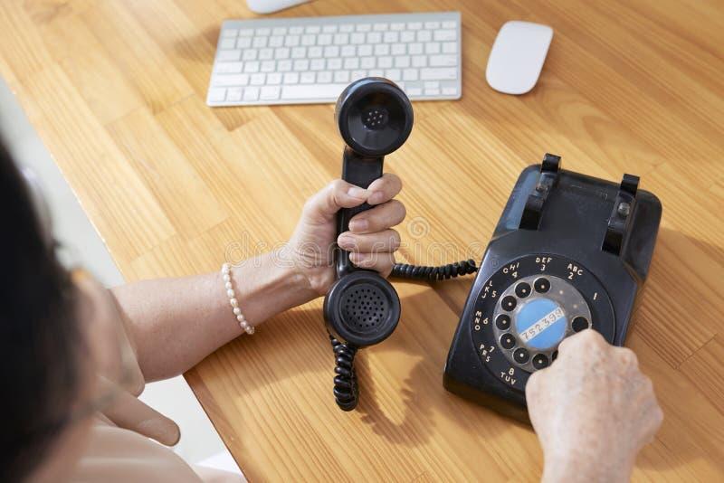 女实业家谈话在减速火箭的电话 库存照片