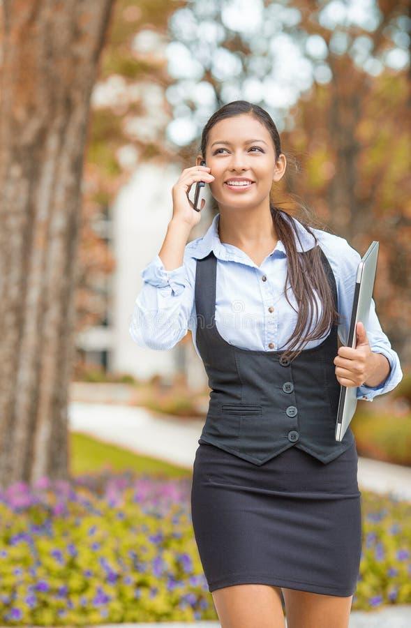 女实业家谈话在手机外面在城市街道上 免版税库存照片