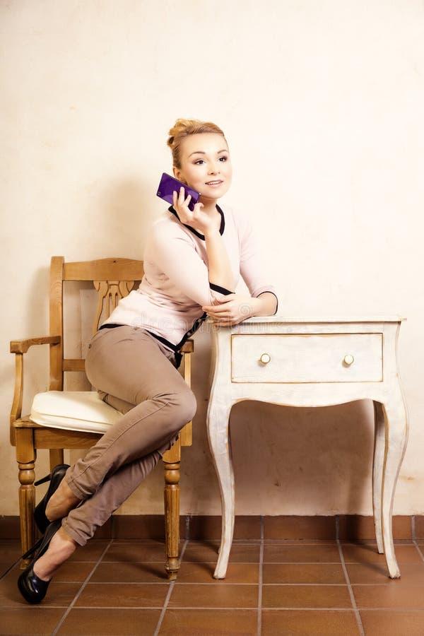 女实业家谈话在手机智能手机 库存图片