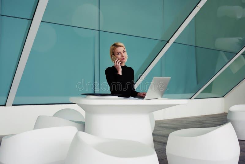 女实业家谈话在手机,当坐开放网书前面在办公室内部时的 库存照片