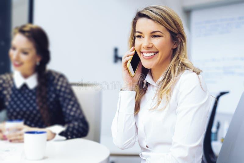 女实业家谈话在电话在办公室 库存照片
