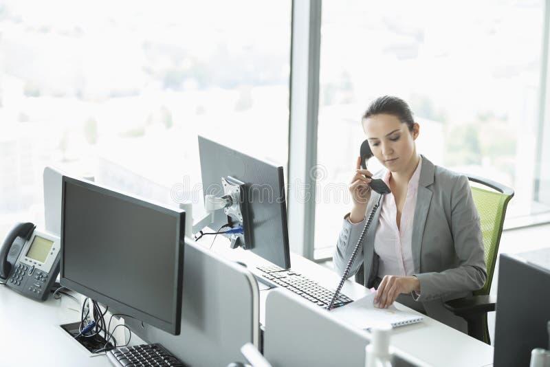 年轻女实业家谈话在电话在办公室 库存图片