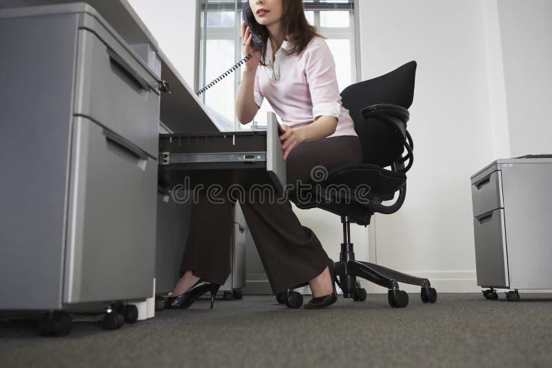 女实业家谈话在电话,当打开抽屉在Offic时 库存照片