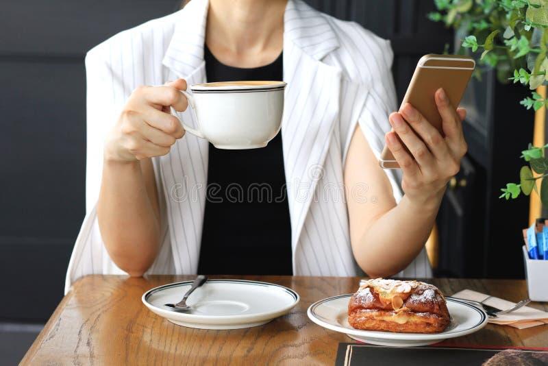 年轻女实业家饮用的咖啡和使用巧妙的电话在咖啡馆,工作在她的在咖啡馆酒吧的咖啡休息的女商人 免版税库存图片