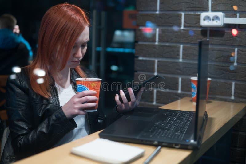 女实业家,研究在咖啡馆,举行智能手机在手上,笔,用途电话的膝上型计算机的女孩 : 在网上, 图库摄影