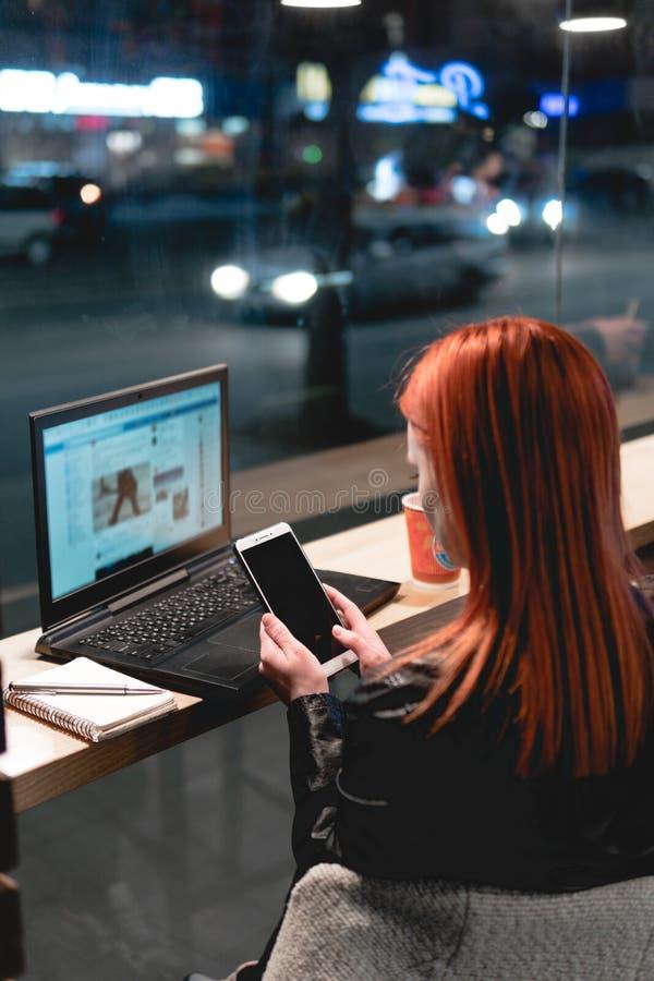 女实业家,研究在咖啡馆,举行智能手机在手上,笔,用途电话的膝上型计算机的女孩 : 在网上, 免版税库存图片