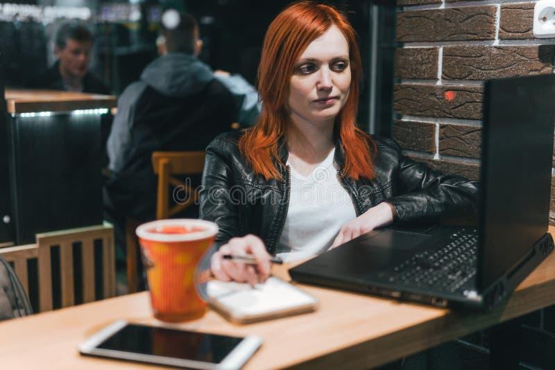 女实业家,研究在咖啡馆,智能手机,笔,用途计算机的膝上型计算机的女孩 : 网上营销, 库存图片