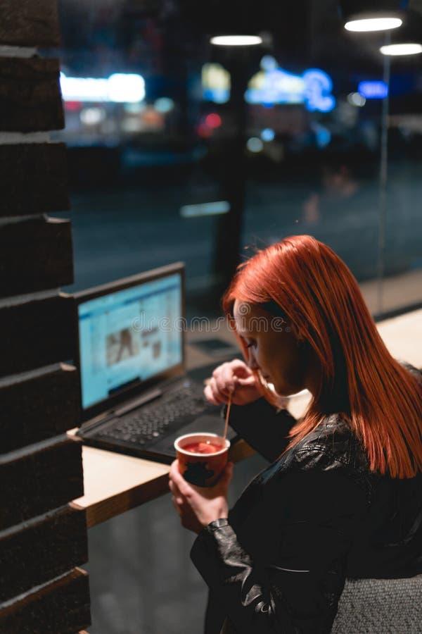 女实业家,研究在咖啡馆,智能手机,笔,用途计算机的膝上型计算机的女孩 : 网上营销, 免版税库存照片