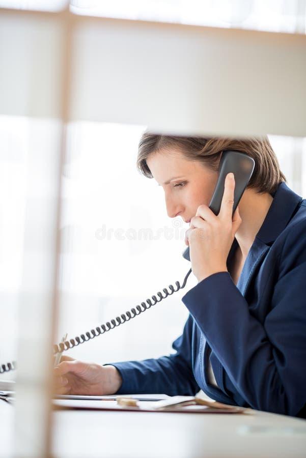 年轻女实业家说在电话里 免版税图库摄影