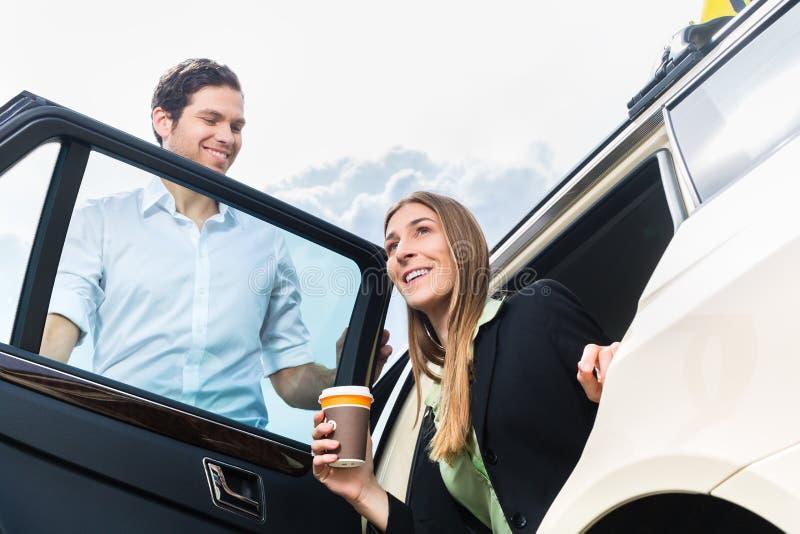 年轻女实业家离开出租汽车 库存照片