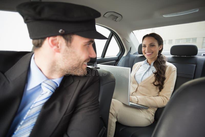 年轻女实业家chauffeured,当工作时 库存图片