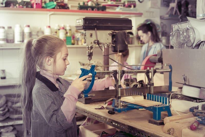 女小学生与木头一起使用 库存图片