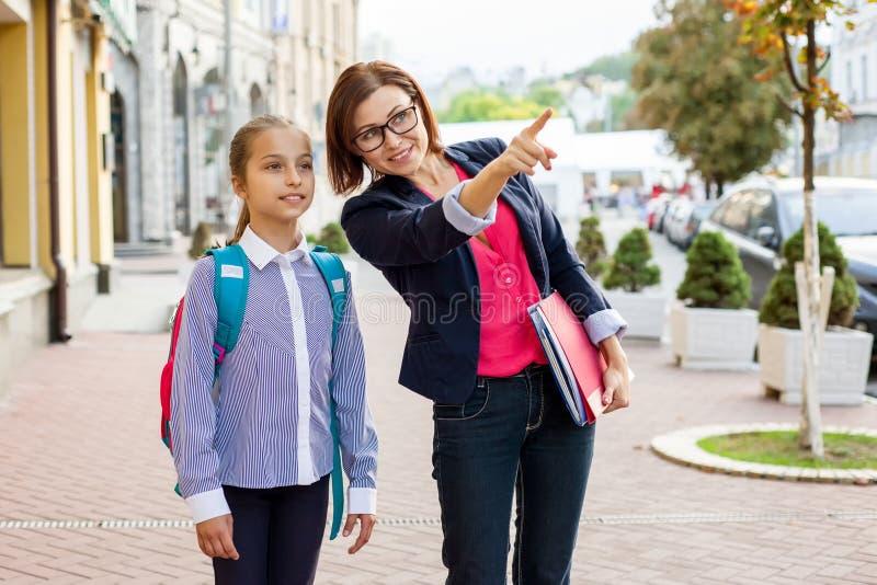 女小学生和老师室外画象  免版税图库摄影
