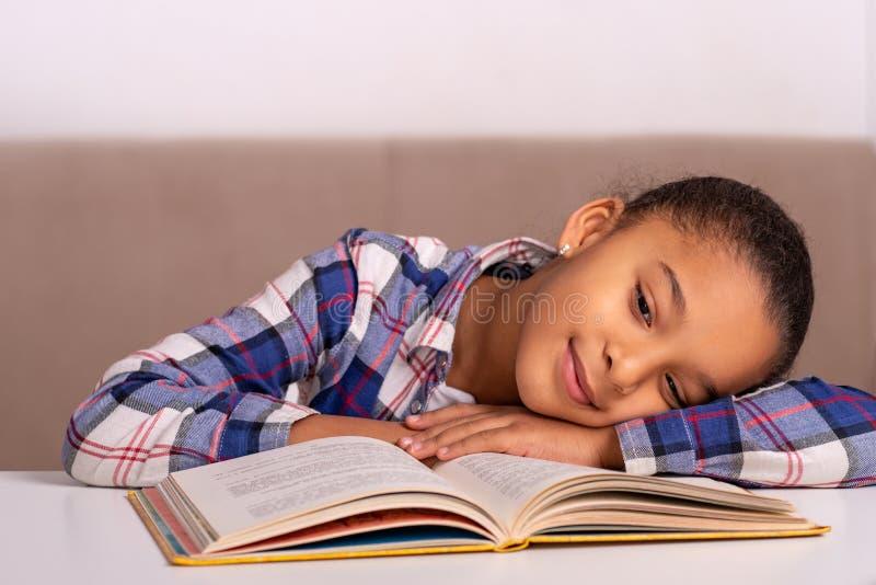 女小学生在家坐在桌上并且做他的家庭作业 免版税库存照片