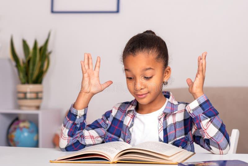 女小学生在家坐在桌上并且做他的家庭作业 库存照片