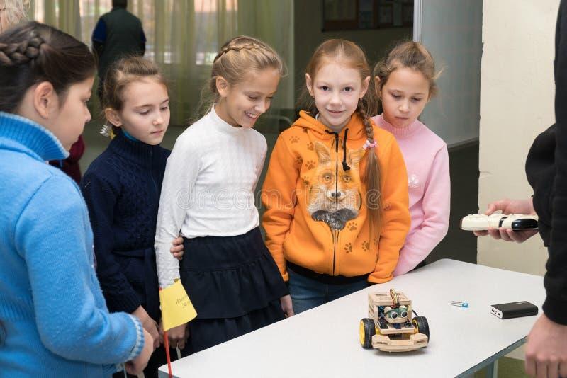 女小学生女孩是微笑和看一个自创汽车模型 库存图片