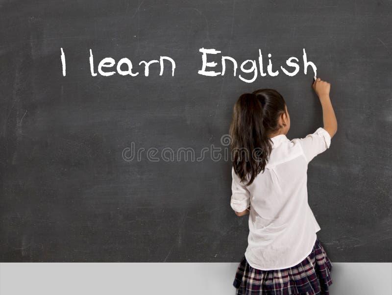 女小学生文字我学会与白垩的英语在黑板学校 免版税库存照片