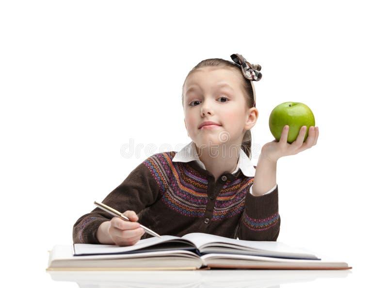 女小学生用一个绿色苹果 免版税库存照片