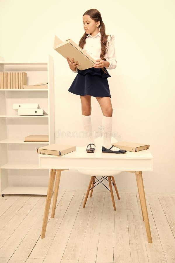 女小学生立场桌工作档案文件夹 逗人喜爱的矮小的书痴 学习历史的学生读了档案文件 ?? 库存照片
