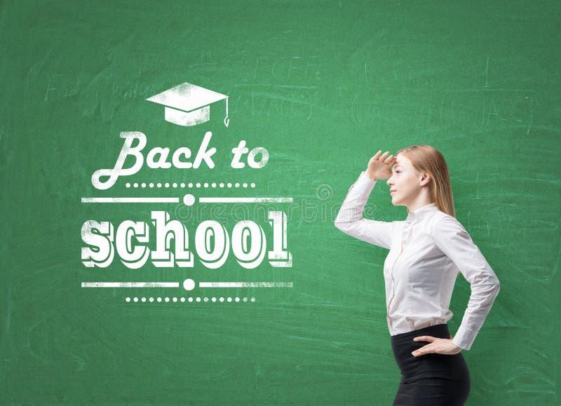 女小学生通过空气看 词'回到学校'在绿色黑板被写 免版税图库摄影