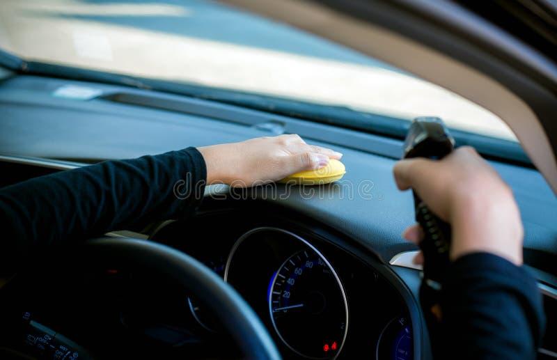 女工在仪表板里面的清洁汽车 免版税图库摄影