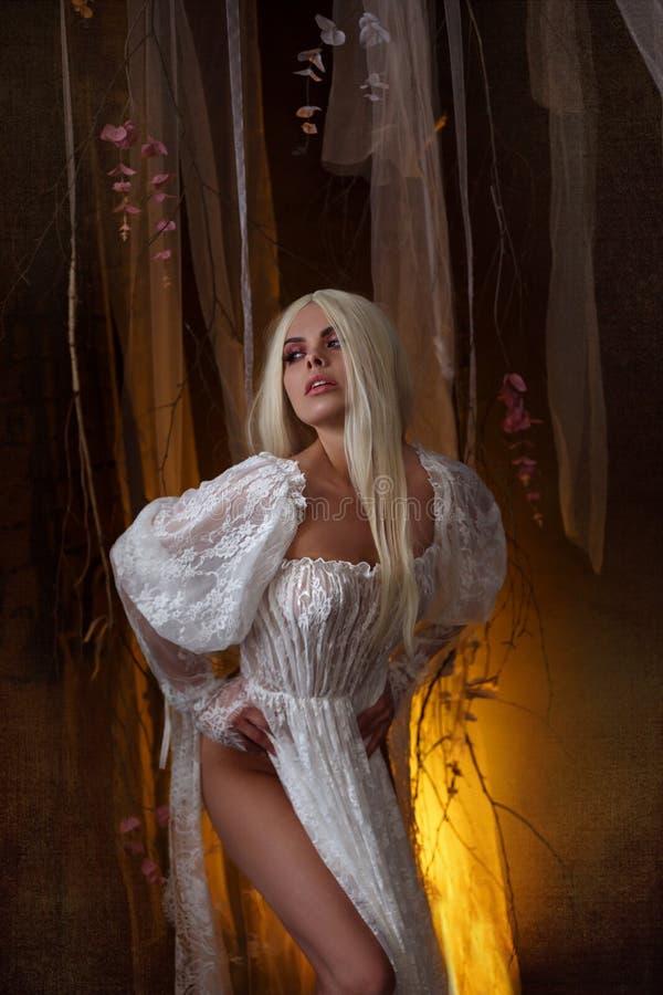 女巫神仙 白色葡萄酒礼服的苍白白肤金发的女孩 诱人的公主,当性感,长的腿摆在反对 图库摄影