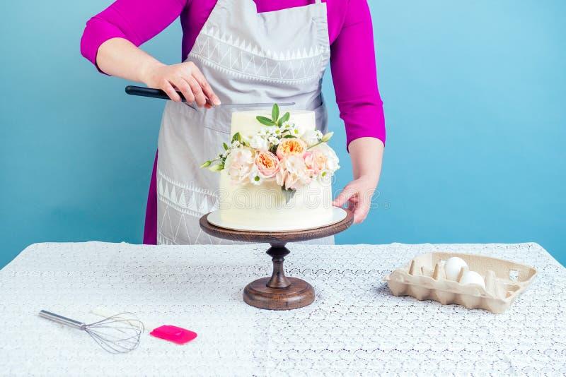 女式糕点师装饰开胃的奶油白双层婚庆蛋糕上装饰鲜花 库存图片