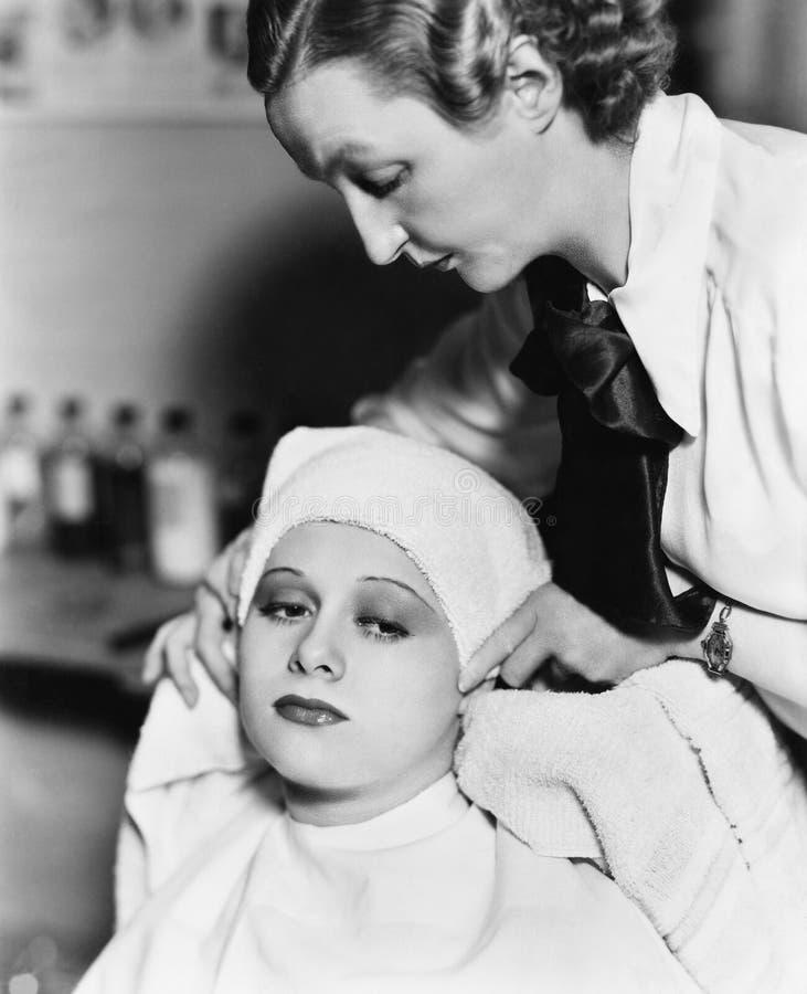 女性一个少妇的美发师干毛发有一块毛巾的在发廊(所有人被描述不是更长生存和没有e 库存图片