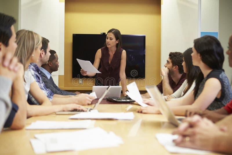 女性上司发言在会议室表附近 库存图片