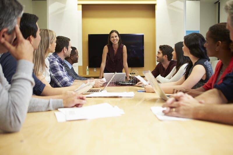 女性上司发言在会议室表附近 免版税库存图片