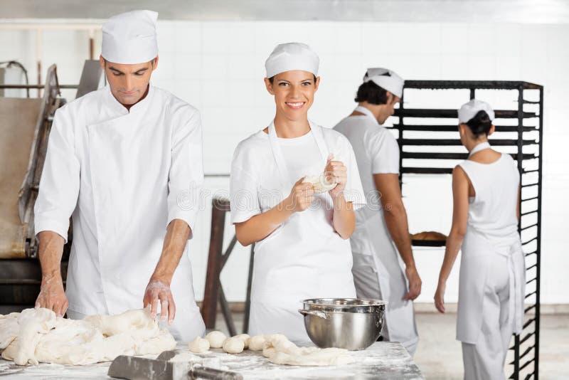 女性与同事的贝克揉的面团在面包店 库存图片