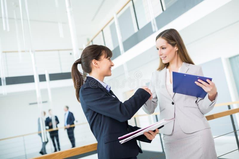 女性专业与同事握手在办公室 免版税库存照片