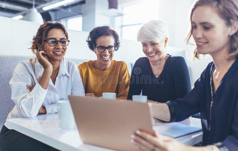 女性专家队在有膝上型计算机的自助食堂 免版税图库摄影